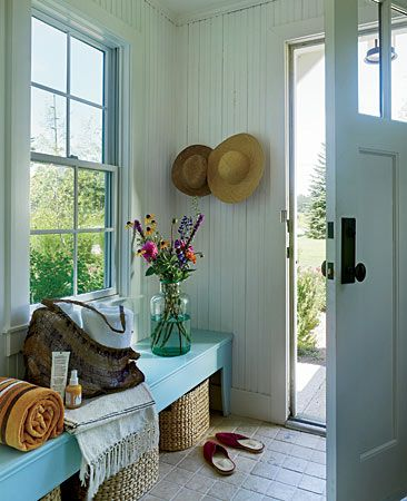 In a cottage in Three Oaks, Michigan, interior designer Julia Edelmann took wainscoting all the way up to the ceiling and put baskets under a rustic turquoise bench to make the space homey and casual.