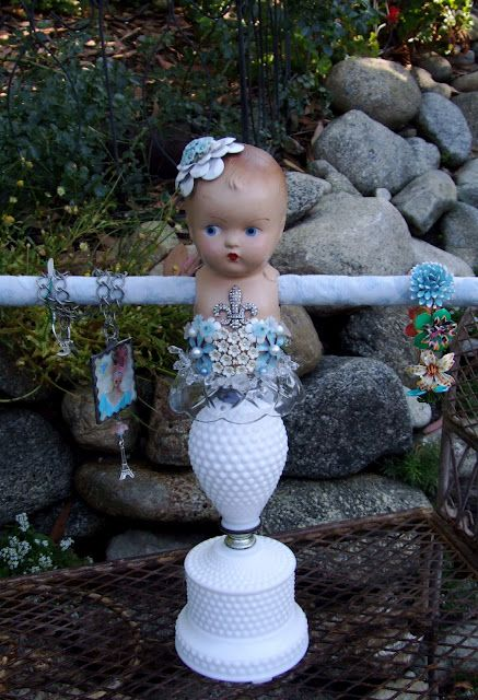 Doll, hobnail milk glass lamp base, and a bar for a creative jewelry display.