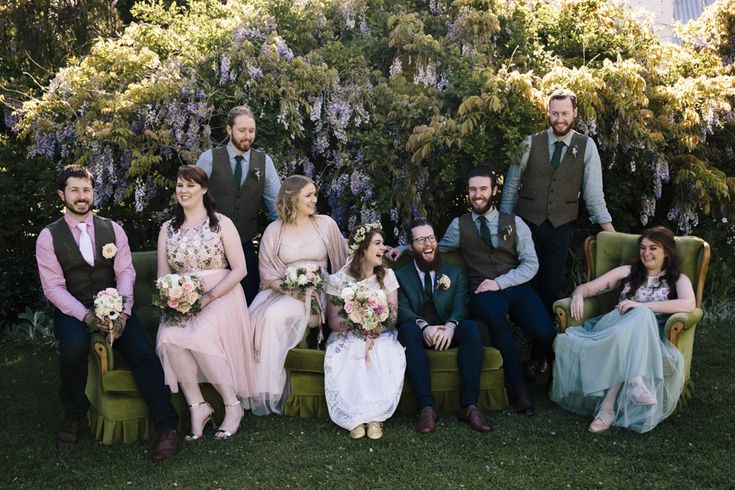 Bridal party laughing on couches like the friends TV series. Bridesmaids wear tulle skirts, sequinned and beaded tops in pastel colours. Groomsmen wear green. Flowers by Barton Flower Bar