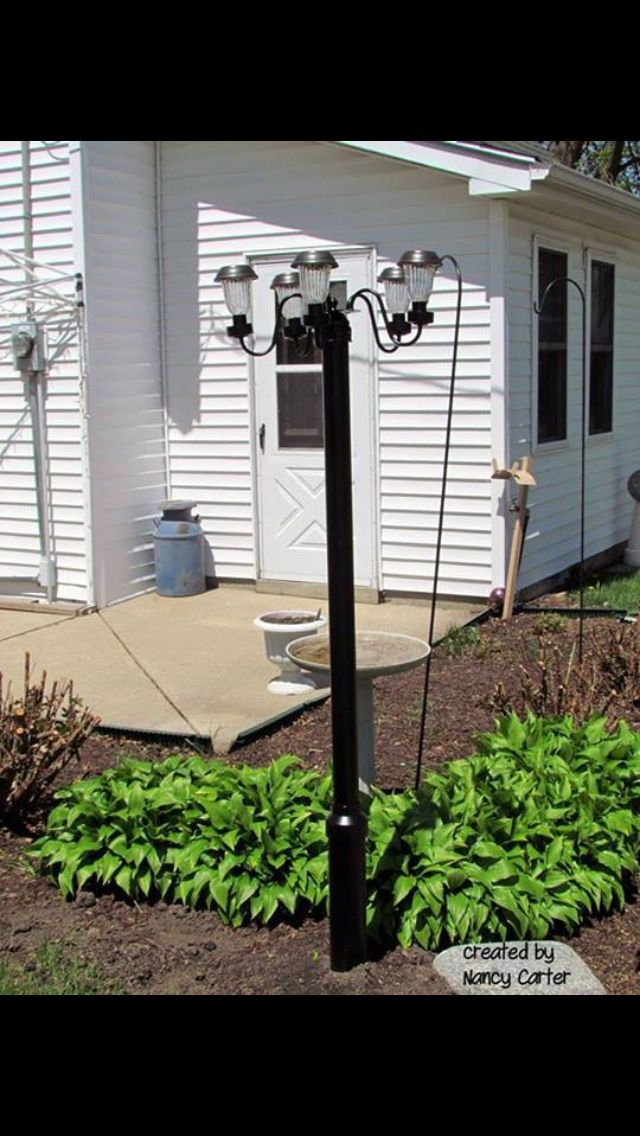 Outdoor solar lighting by nancy carter Make a pole out of PVC pipe  paint it black.  Strip all the wiring of a chandelier  paint it black.  Turn the chandelier upside down  attack it to the pole. Place solar lighting in each cup.