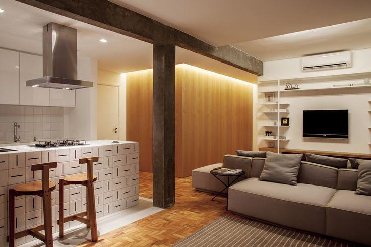 Reforma de apartamento antigo em São Paulo com todos os ambientes integrados. Cozinha, living, jantar e Hometheater em um único espaço, ideal para receber amigos e tem espaços mais amplos. acabamentos em branco, madeira e concreto. Decoração minimalista e contemporânea com referências scandinavas