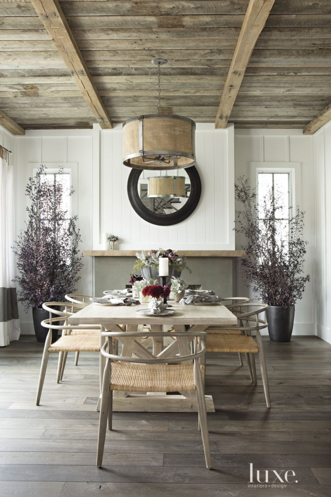 Inspired by Napa Valley, architect Eric Olsen gave a family's Newport Beach home a modern farmhouse style. William's Wood Works fabricated the tongue-and-groove ceiling in the living room, where glass-front cabinets flank a fireplace. The coffee table and black table lamps are from Big Daddy's Antiques.
