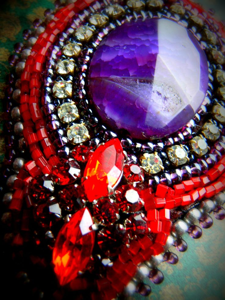 Magenta velká vyšívaná brož v červenofialových odstínech. Její dominantou je velký kabošon (40x30mm)fialového chalcedonu s krásnou kresbou... ten je obšit fialovými a červenými korálky a stříbrnobílým štrasem, ve spodní části je pevně přilepen štrasový knoflík v rudých odstínech.. část je dále obšita korálky a dvěmi řadami rokajlu.. část je podlepená ...