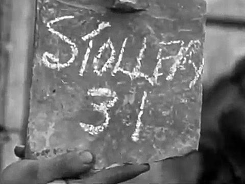 Sergeant Jack A. Stollery MM. Taken crossing the Ante River during the assault on Falaise. Seems to be written on a broken roof tile.