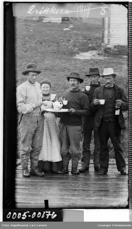 Mer info om ftografen enn om folka. Altså. Er ikke nødvendigvis anleggsarb. Gruppebilde av fire menn og en kvinne som har kaffepause.