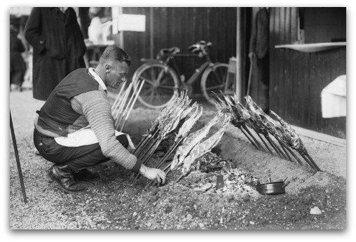 BARBECUE: A man tends to grilled fish over an outdoor fireplace at the 1928 #Oktoberfest #history