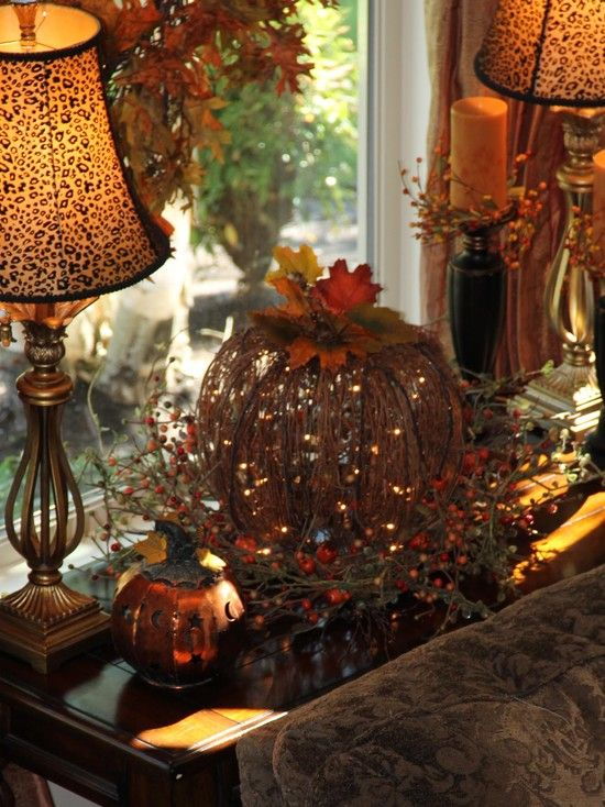 Fall decor / a big light up pumpkin center stage on a table, planked it with two lamps, added two candles, and a metal pumpkin on the other side. It looks really cute at night.