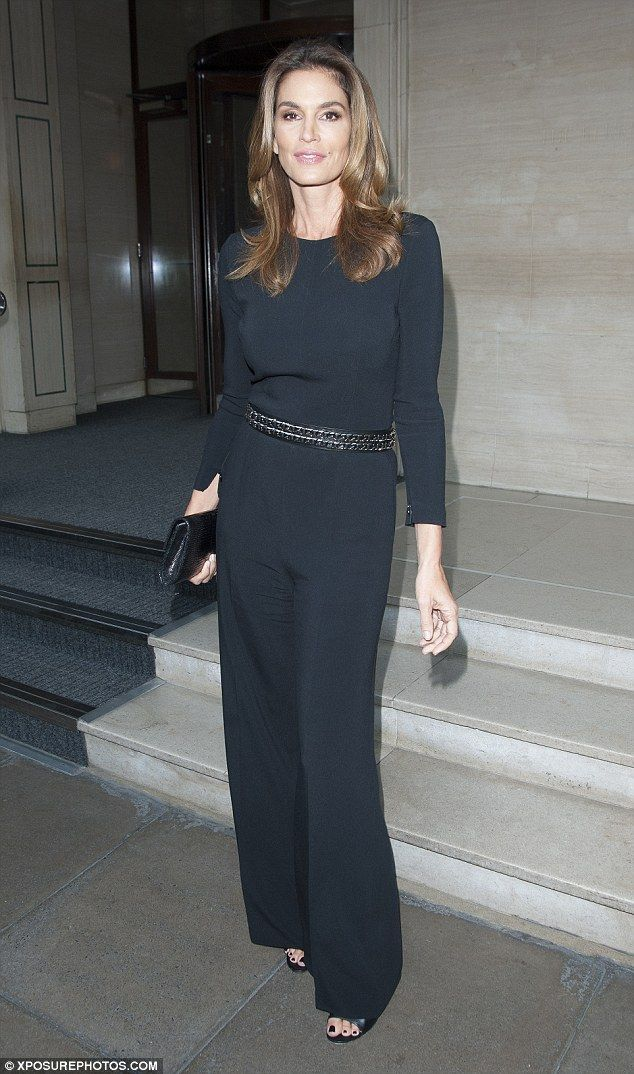 Working it: The youthful 49-year-old looked stunning in a snug black jumpsuit with wide-le...