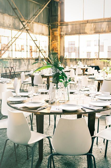 "The gorgeous dinner setup. ""During dinner, we decided to use a minimalist style that allowed the rad rusted colors and natural light of the building to really take center stage,"" says Ceccarelli. ""We loved the simplicity of the single palm leaves, especially when set against our matte white color palette — it highlighted the space with a clean, modern look, which worked well in that airy, industrial dinner location."" #refinery29…"