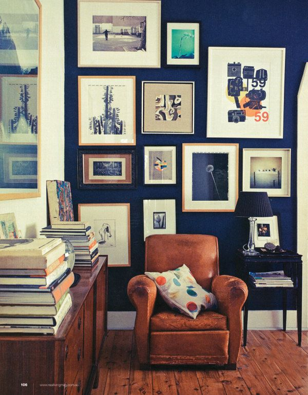 Dark royal blue wall, collection of pictures on wall, leather chair, books via:dustjacket attic: Interiors | Modern | Retro