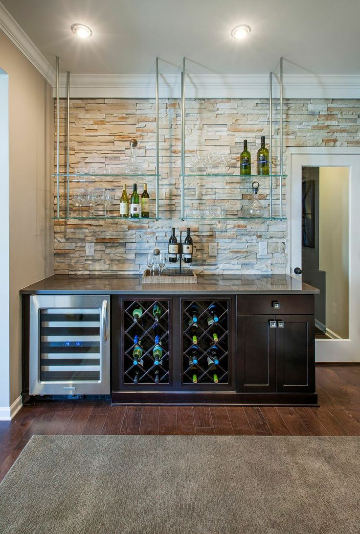 Create a dynamic home bar with floating glass shelves that contrast the light stone accent wall and dark wood cabinets. Seen in Waterstone, a Raleigh community.