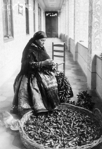 Peasant's wife strings paprika onto cord for drying in Sarkoz, Tolna District, Bulgaria