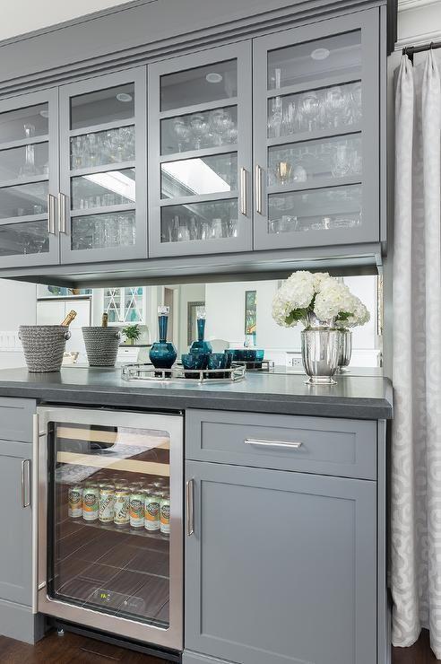 Gray bar cabinets with mirrored backsplash