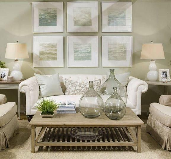 Soft green beachy coastal living room design with white gourd lamps, White chesterfield tufted sofa, recycled green glass bottles vases, sisal rug, accent end tables, beige accent chairs, coffee table, beachy blue green art gallery and soft green walls paint color.