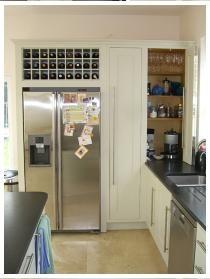 Housing for American fridge freezer with integral wine rack, tea and coffee cupboard with bifold door shown open.
