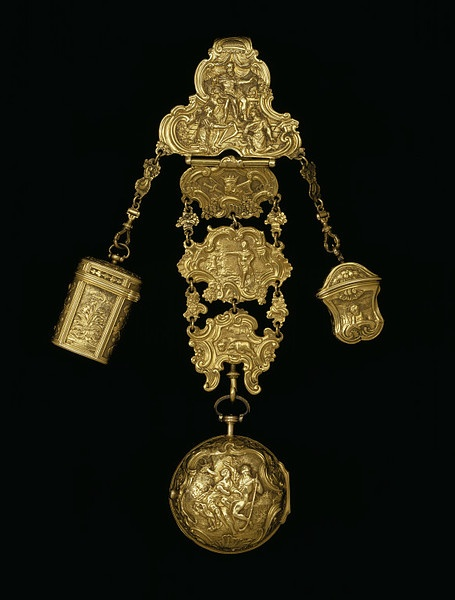 *Chatelaine ca. 1730-1750, Gold. A long hook at the back to hang from the belt of a fashionable lady. London hallmarks on the hook precisely to 1755-6. There are 3 objects suspended from the chatelaine. Middle: A watch, which bears the name of the watchmaker, Robert Cawley, Chester, movement no. 91. The watch and the small empty container or étui on the right are of approximately the same date as the chatelaine. The étui for snuff, ca.1730 contains a small gold spoon for ladling out the…