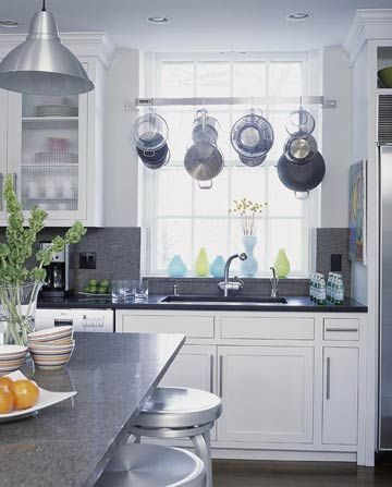 """Pot Rack over the Sink - """"This stainless-steel pot rack placed above the sink makes it simple to wash pots and hang them up to dry in the same spot. Making it easy to clean means it is more likely that pots and pans will not be left out. This kitchen organization tactic is perfect for those who find the chore of cleaning a difficult one. The window in front of the sink and pot rack provides an enjoyable view to make cleanup less of a hassle"""""""