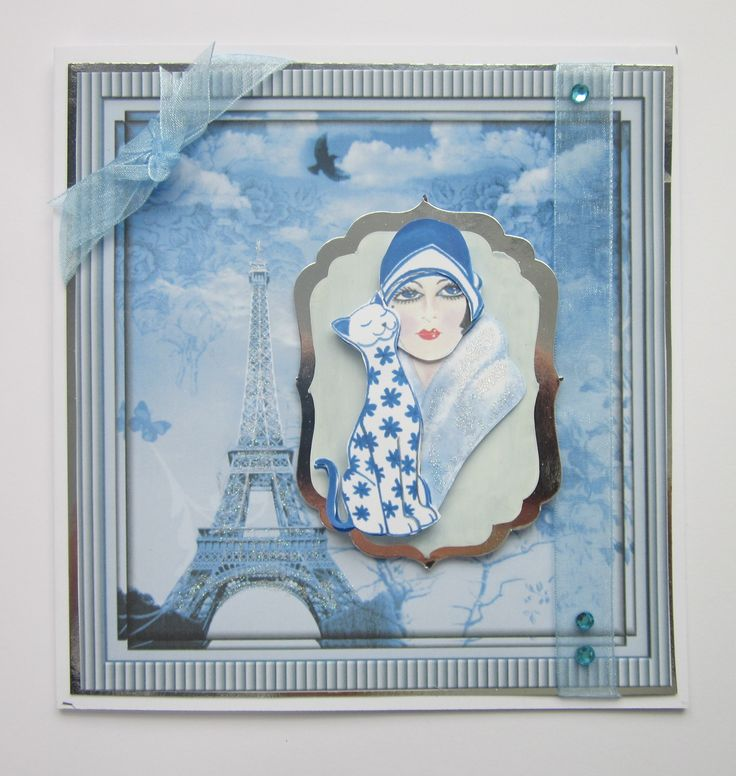 Deco NV57 Your choice of sentiment when ordering. 7×7. The main picture image has been built up in layers and affixed to a silver shaped mat. This has been mounted on a backing picture of the Eiffel Tower. Blue ribbon and gems added for decoration with glitter highlighting the Eiffel Tower. Insert included. £4 Please …