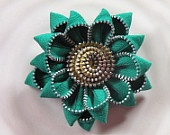photo of item on plate Black Up Cycled Vintage Zipper Flower Brooch or Hair Clip. $15.00, via Etsy.