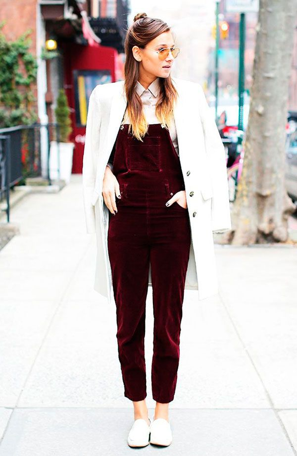 Street style look com macacão jardineira vermelho de veludo, camisa branca, sapato branco e sobretudo.