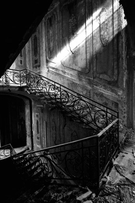 faded glory, decrepit, deteriorating architecture, former grand staircase, wrought iron, black and white, sad, abandoned