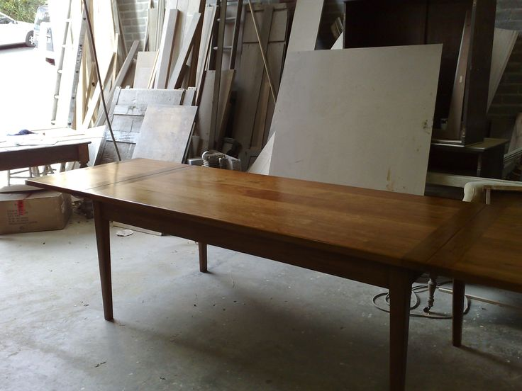 Classic dining table in cherry wood with tapered legs, extensions at either end.