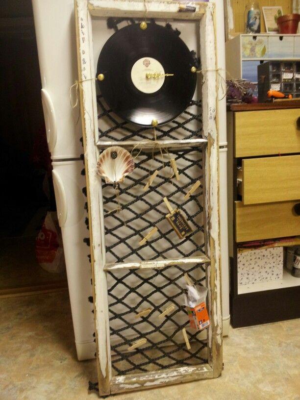 Gjenbruk. Gammel vindusramme, bakside dekket med taunetting. Øverst, LPplate med urverk. Dekorert med skjell, gammel eske og en bit rakved