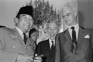 """Portrait of Ellsworth Bunker, Howard P. Jones and President Sukarno Original caption: U.S. Special Envoy Ellsworth Bunker, right, and Ambassador Howard P. Jones, center, chatting with Indonesian President Sukarno April 6, 1965, at the Presidential Palace in Djakarta. The Americans met with Indonesian officials in efforts to stop the """"decline"""" of U.S. Indonesian relations. Image: © Bettmann/CORBIS Date Photographed: April 6, 1965"""