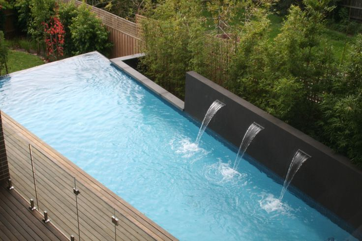 Swimming pool with water feature wall and backdrop of for Pool design website