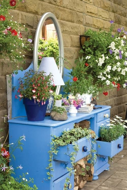 Potting bench     What's Old is New Again: An old painted dresser gets a new life as a tiered funky planter, while the space underneath is used for storing firewood. An idea for upcycling furniture in an undercover outdoor space. More clever plant container ideas @ http://themicrogardener.com/clever-plant-container-ideas/ |The Micro Gardener