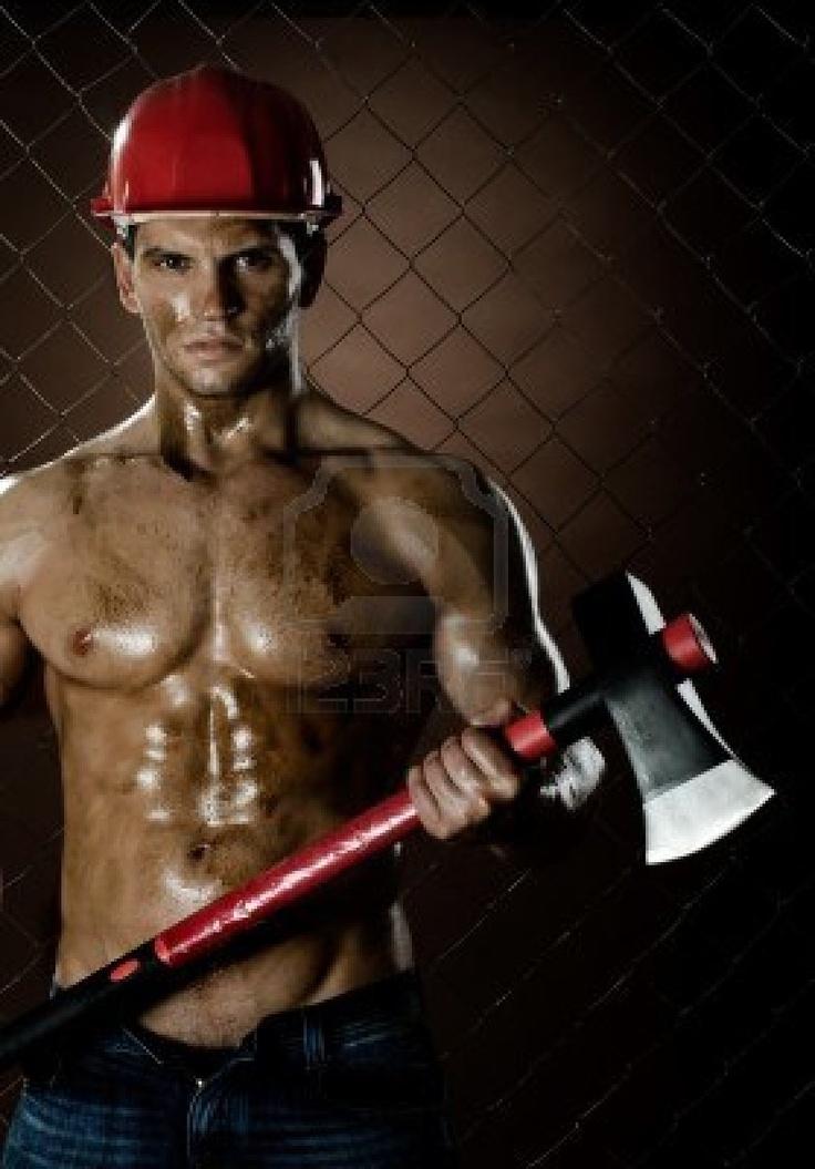 krása svalnatý dělník chopper muž, v bezpečnostní přilbou s velkým těžkým sekyrou v ruce, o vypořádání plotu pozadí Reklamní fotografie