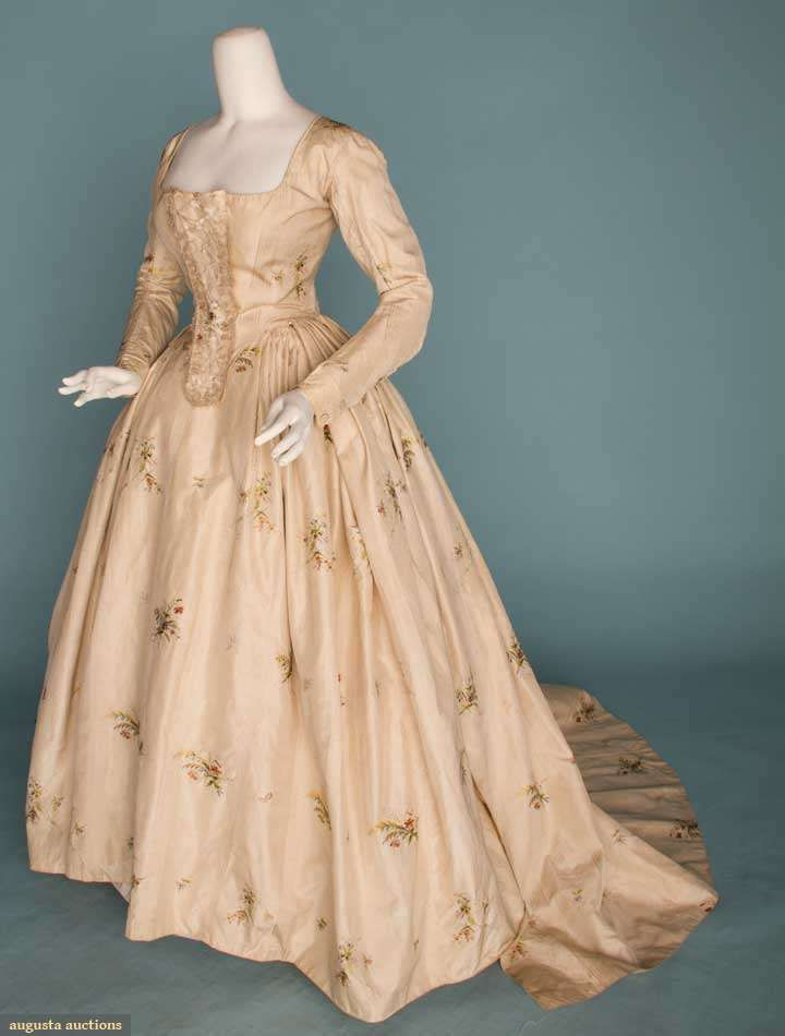 ca 1770-1790 3-piece robe a l'anglaise of cream silk damask w/woven in brocade sprays of polychrome flowers. Lace front bodice w/attached back skirt train, pleated petticoat, and original stomacher w/ribbon & lace trims. Fabric woven in the 1770s, bodice altered in 1790s small breaks in fabric along arm seams, but overall in very good condition..