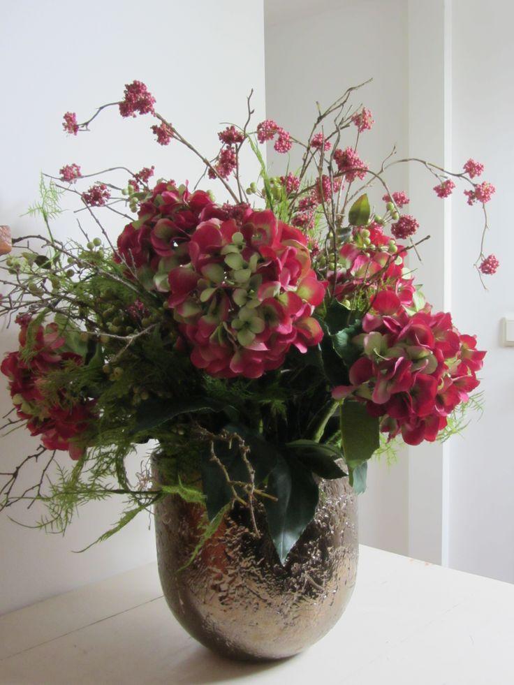 Prachtige combinatie van roze hortensia's, roze bessentak en groen in bronskleurige pot. www.abonneefleur.nl