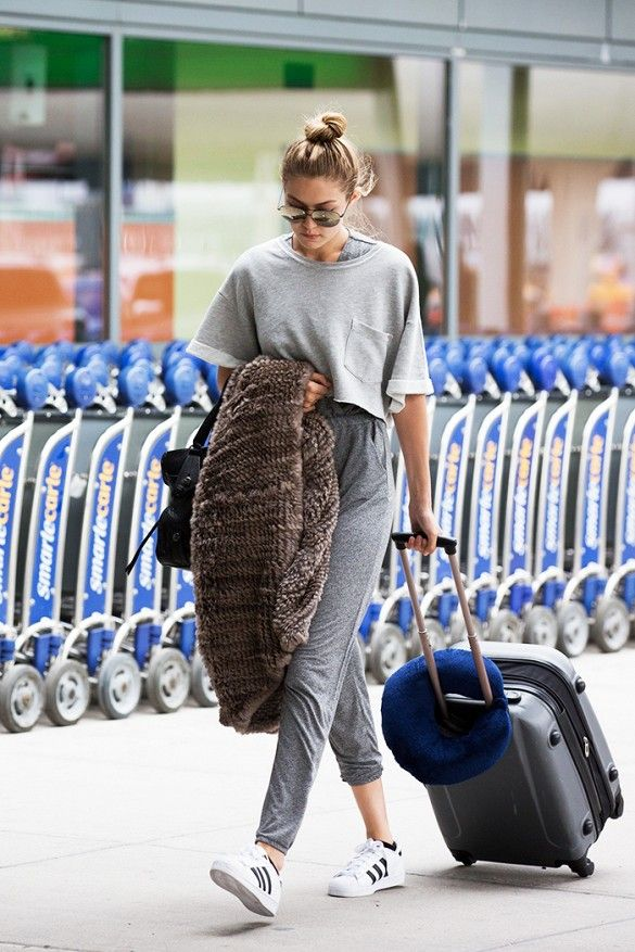 Gigi Hadid wears a cropped grey t-shirt, grey joggers, tennis shoes by Adidas, sunglasses and a black handbag.