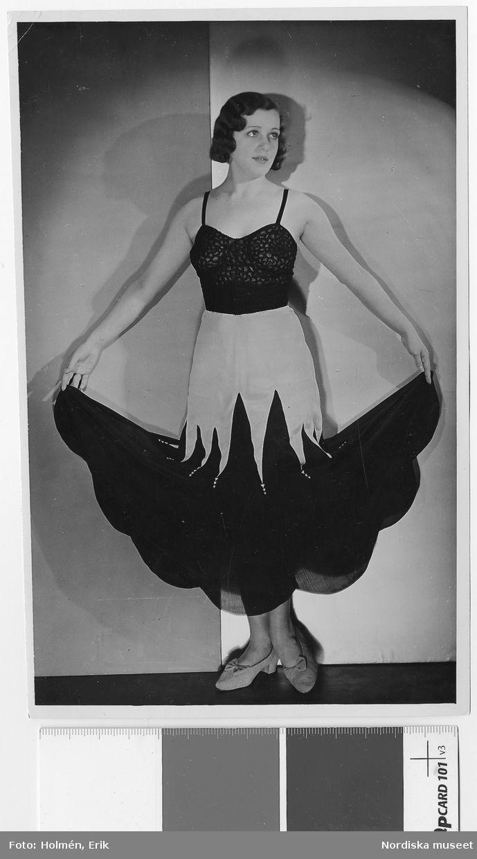 Kvinna i underkläder. Underkjol av rosa och svart crepe de chine. Parismodell. Nordiska Kompaniet. Fotograf: Erik Holmén.