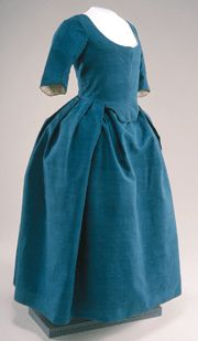 Blue dress, New England, 1775-1795.   Woman's one-piece robe á l'anglaise (round gown) in blue wool tabby, with the waist seam entirely bisecting bodice and skirt. The skirt is made up of three selvage-to-selvage widths, and is box-pleated into the waist seam all around. The gown has three-quarter-length sleeves, and a square neckline in front and back. Museum Collections Fund.  New England Antiques Journal - collection at Historic Deerfield