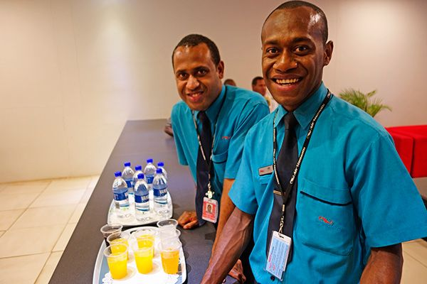BIG SMILES all round as Air Vanuatu flight attendants Basil and Tom serve guests attending the arrival of our second ATR72-500 at Port Vila Airport.