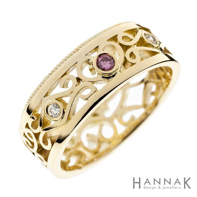 Pitsi -vihkisormus | Keveän ilmava ja koristeellinen filigraanityylinennäyttävä vihkisormus, jossa sormuksen toistareunaa kiertävä punoson saanut parikseen kiiltävää pintaa. Keltakultainen sormustukee vaaleanpunaisen safiirin lämmintä sävyä.