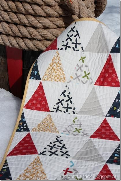 Solid white in between prints triangles. Great Christmas Quilt!