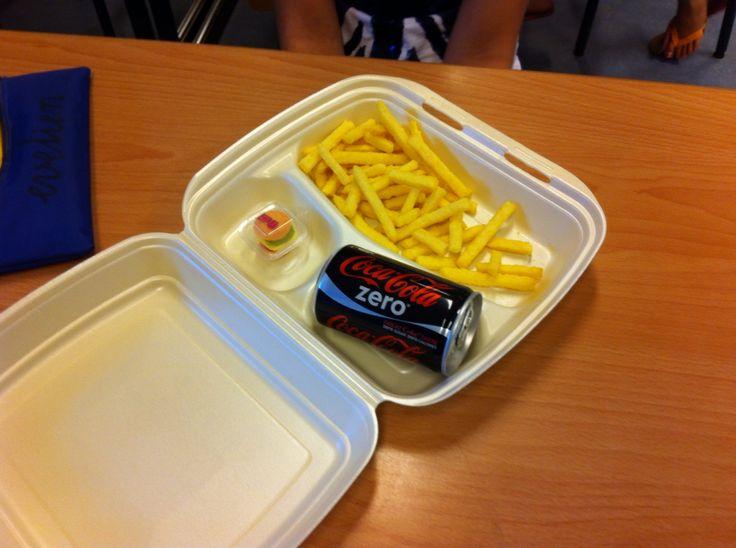Traktatie van kind. Chipsfrietjes, mini blikje cola, snoep hamburger in een snackd oos. Erg leuk!