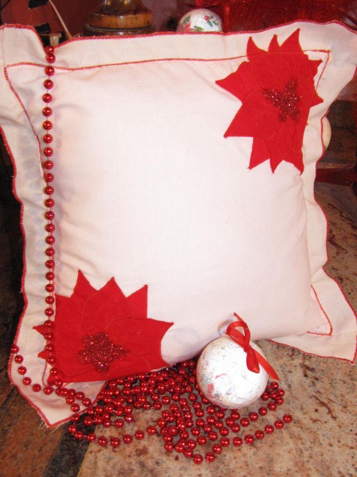 ciao a tutti questo bel cuscino natalizio l ho realizzato con stoffa,applicazione e l intero contorno lavorato con punto zig zag.al centro del fiore ho spruzzato dei brillantini per dargli il un po di movimento.