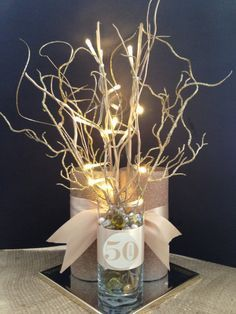 Fiftieth wedding anniversary party centerpieces.  Add branches and vase filler to a clear glass cylinder vase for a simple and beautiful centerpiece.
