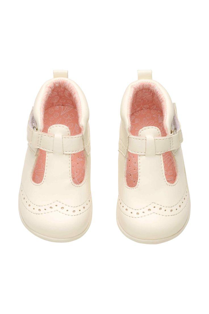 Buty do nauki chodzenia: Buty z imitacji skóry dla dzieci zaczynających chodzić. Patka na rzep z boku. Wyściółka z bawełnianej popeliny. Gumowe podeszwy.