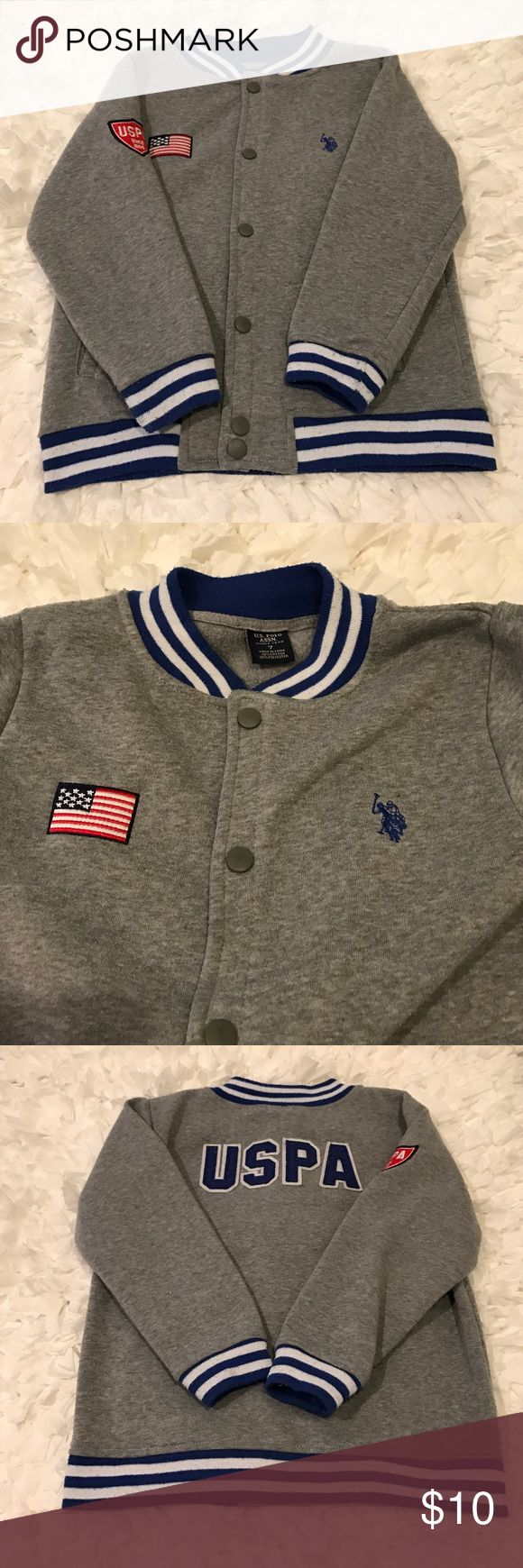 Boy's U.S. Polo Assn. Jacket Adorable Boy's U.S. Polo Assn. light Jacket. Size:7. Gently used there is some pilling on Jacket from washing. No stains, rips, tears etc. & price reflects. Color is heather gray with blue & white stripe hem, cuffs & collar. Snap button front closure. 2 front pockets. Blue logo on chest & American flag on chest. 1 sleeve has logo on it & back of Jacket says in blue & white USPA. Inside lined in gray. Very soft! 70% cotton. 30% polyester. Machine wash. Tumble dry…
