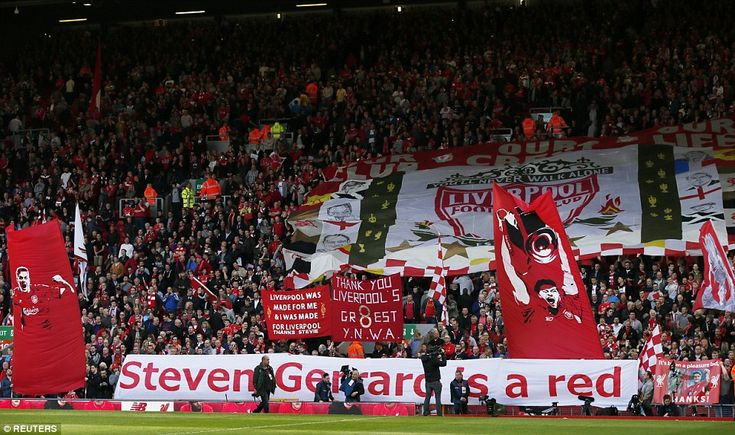 Inspirational: Liverpool fans hold aloft their banners and signs to adorn their talisman S...