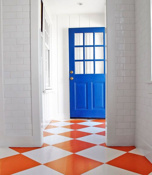 """""""With walls covered in white subway tile, the kitchen in my house on Nantucket was in danger of becoming a white box. To liven things up, I called in decorative painter Audrey Sterk to do these large orange and white squares on a diagonal."""" —Gary McBournie   - HouseBeautiful.com"""