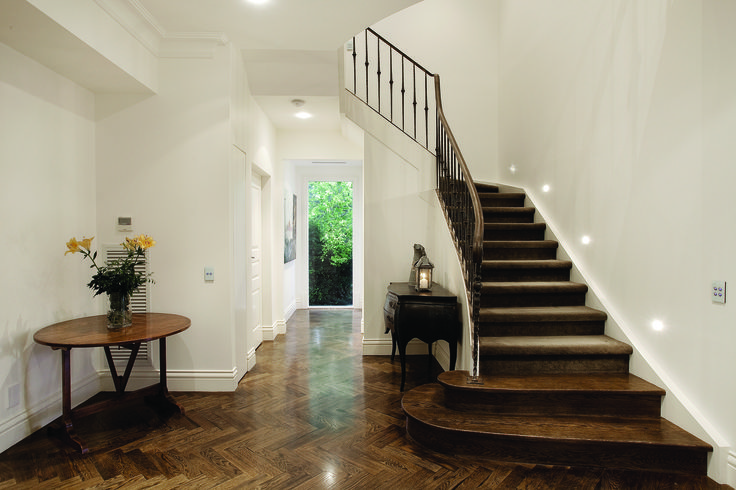 Curved Staircase With Timber Handrail, Raw Iron Baluster, Timer and Carpet Overlay.  Ravida- Property With Distinction