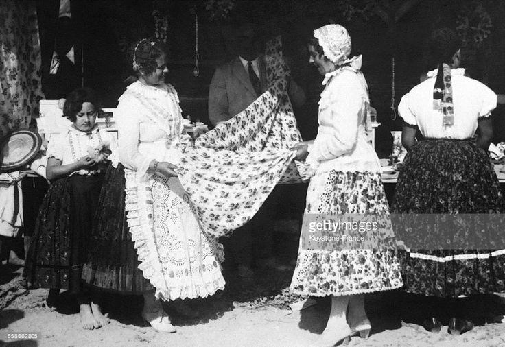 Des paysannes hongroises vendant des tissus tissés à la main qui serviront à confectionner les robes des jeunes filles dont la coutume est de porter au moins trente jupes l'une sur l'autre afin que la robe ressemble quelque peu à une crinoline, à Szeged, Hongrie circa 1930.