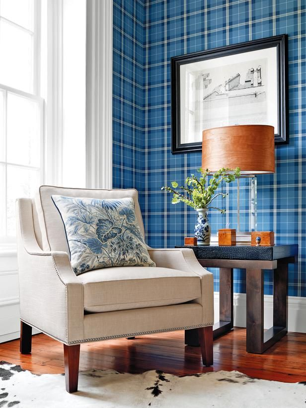 Menswear patterns continue to be trendy, both as upholstery fabrics and wallcoverings. Here, a classic tartan plaid wallpaper in shades of blues gives this sunny corner a sophisticated lounge-like feel. Image courtesy of Thibaut