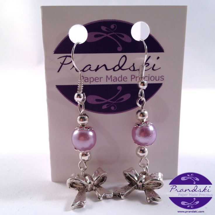 Lilac faux-pearl and Tibetan silverribbon tied in a bow charm onsilverplated ear hook wires.     • Tibetan silver ribbon bowcharm with lilac faux-pearl beadcharms  •Silver platede...